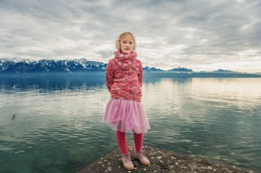 Adorable little girl resting by lake Geneva on a cold winter day, wearing warm pink pullover, tutu skirt, tights and shoes, image taken in Lausanne, Switzerland
