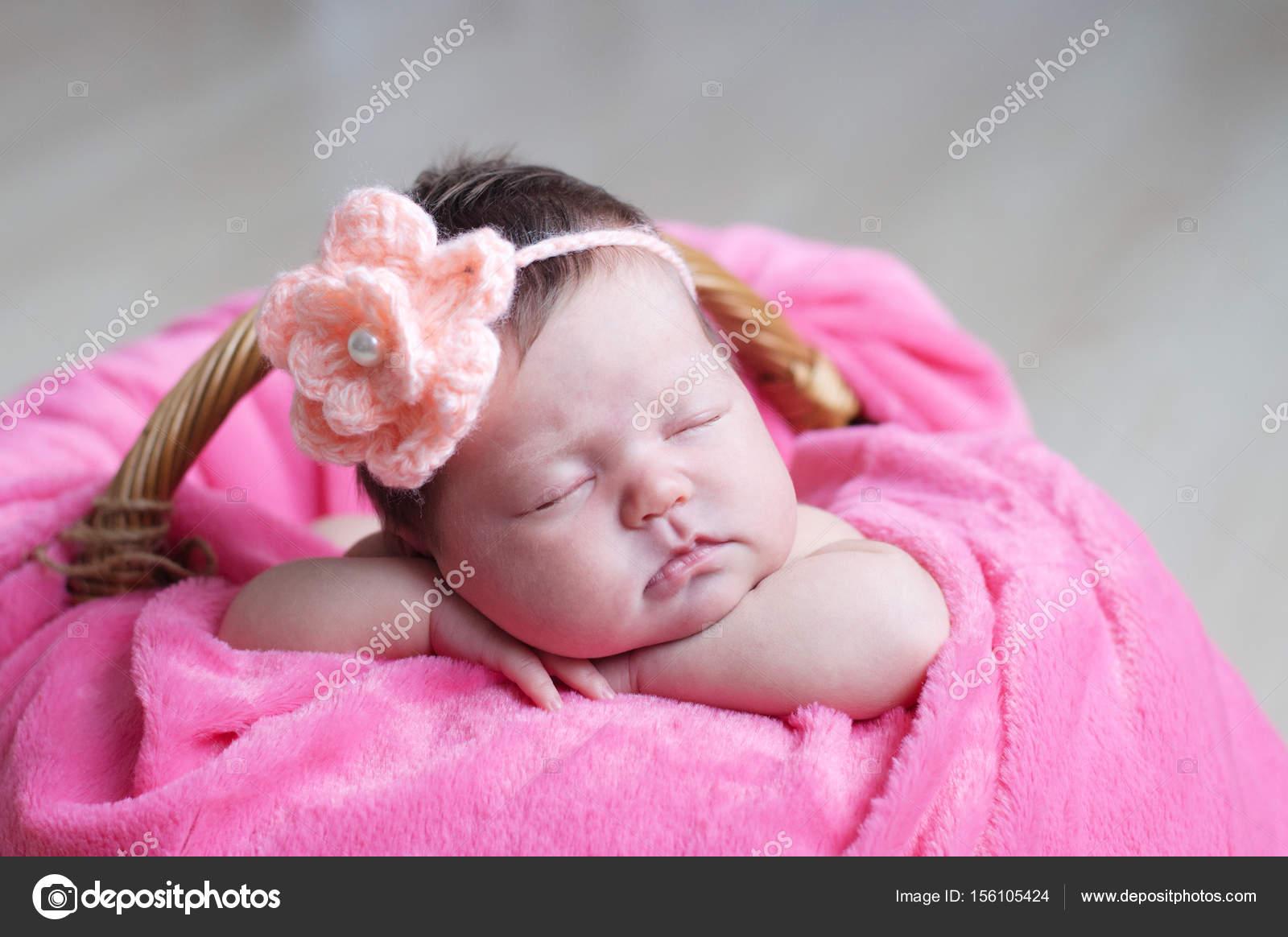 Recién nacido durmiendo con flor tejida en la cabeza. Bebé niña en rosa  manta en e29ffb72e79e