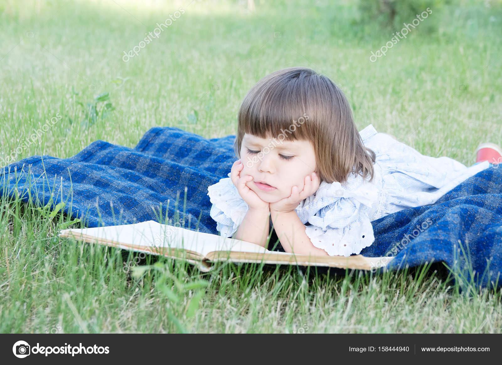 Libro De Lectura Del Niño Acostado Sobre El Estómago Al