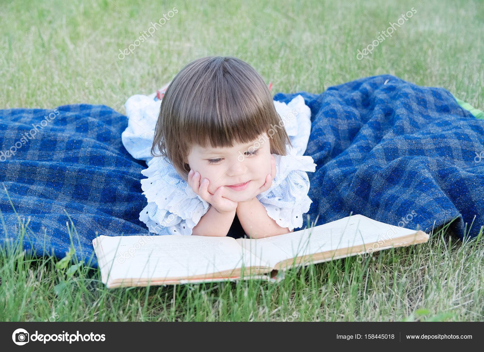 little girl reading book lying on stomach outdoor, smiling cute