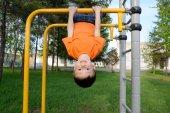 Junge spielt mit dem Kopf nach unten im Freien auf der horizontalen Reckturnhalle. Kind auf dem Spielplatz, Kinder-Aktivität. Kinder haben Spaß. Konzept der aktiven gesunden Kindheit