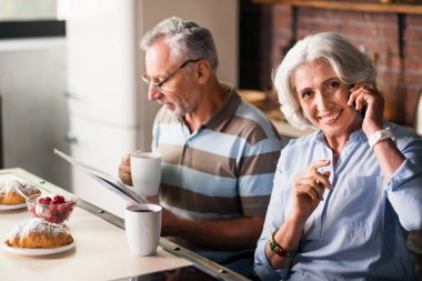 Smiley retired couple having morning coffee in the kitchen