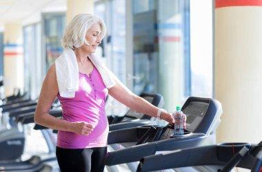 woman standing on treadmill.
