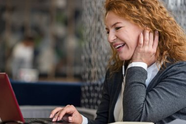 Side view of smiling woman using laptop