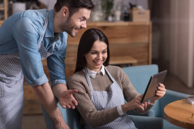 Satisfied overjoyed couple laughing and using tablet
