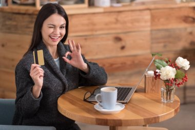 Beautiful delighted woman presenting a discount card