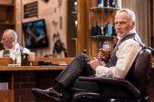 Fotografie Elegante senior Mann mit Whiskeyglas und Zigarre im barbershop