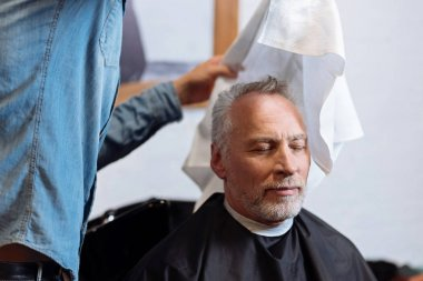 Old man being wiped with towel by barber