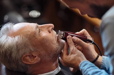 Old man getting his beard shaved by barber