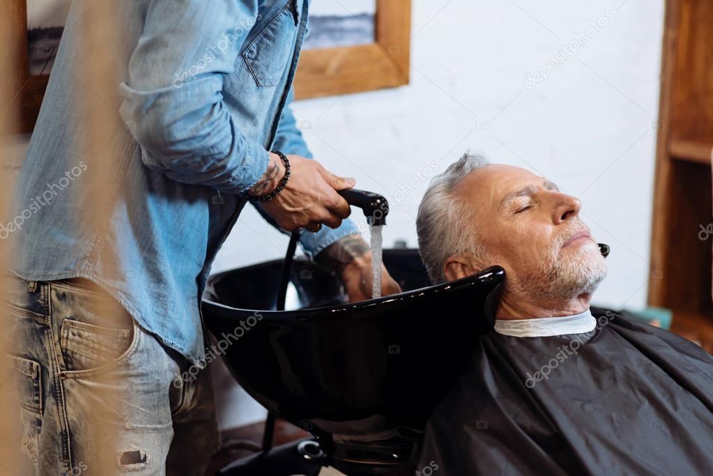 Senior man during washing hair in barbershop
