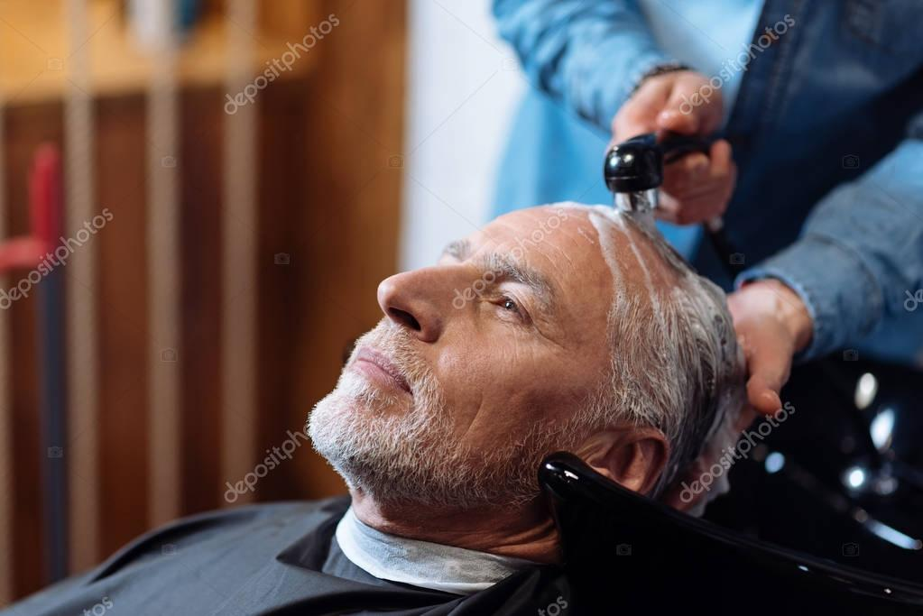 Old man during washing his hair in barber shop