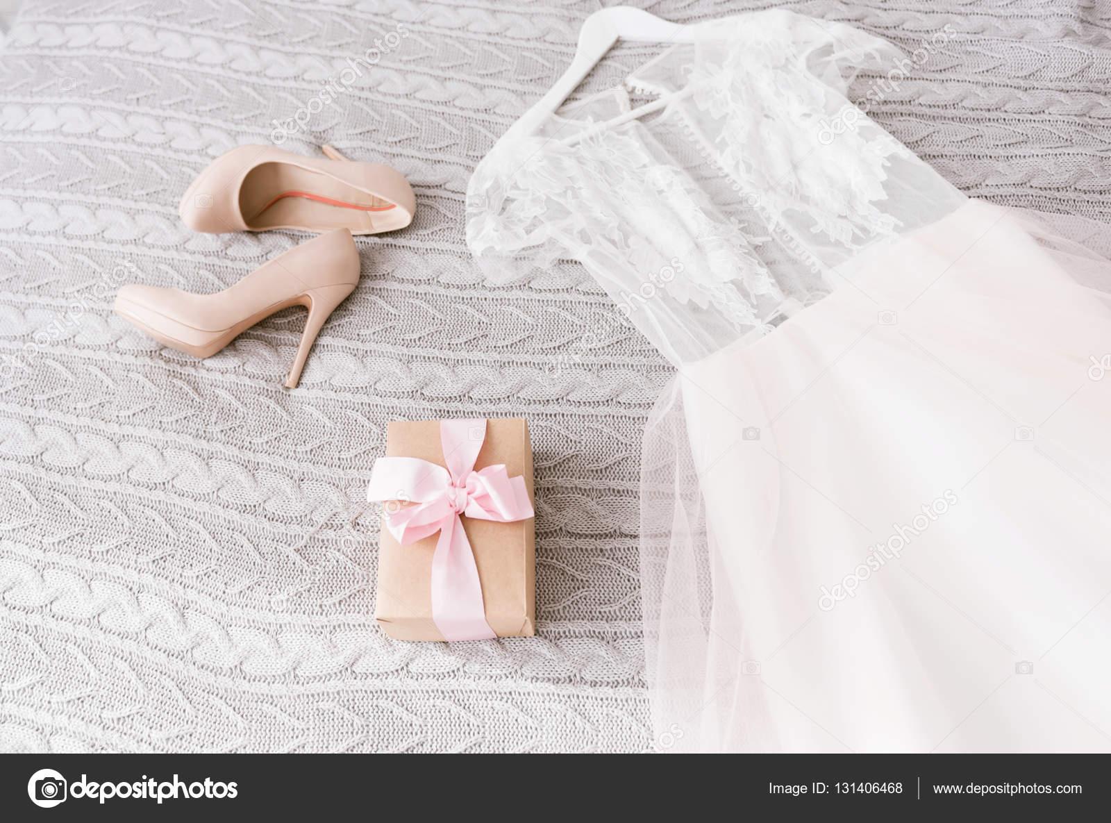 Weiße Hochzeitskleid und Schuhe auf dem Bett liegend — Stockfoto ...