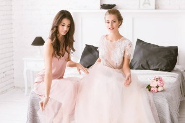 Delighted bride and bridesmaid sitting in the white room