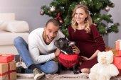 Fotografie Begeistert junge Mann sitzt neben dem Weihnachtsbaum