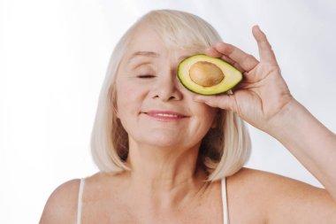 woman holding an avocado half near the eye