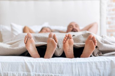 Pleasant non-traditional couple showing their feet