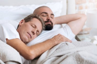 Pleasant non-traditional couple sleeping in the one bed