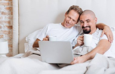 Delighted gay couple using the laptop in the bedroom