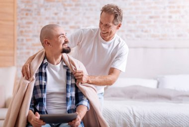 Positive aged man caring about his young partner