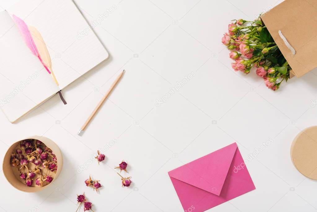 Pink envelope lying near scattered rose buds