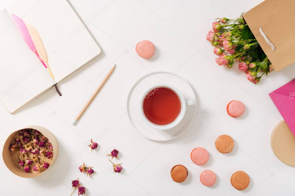 Tea cup being surrounded by macaroons