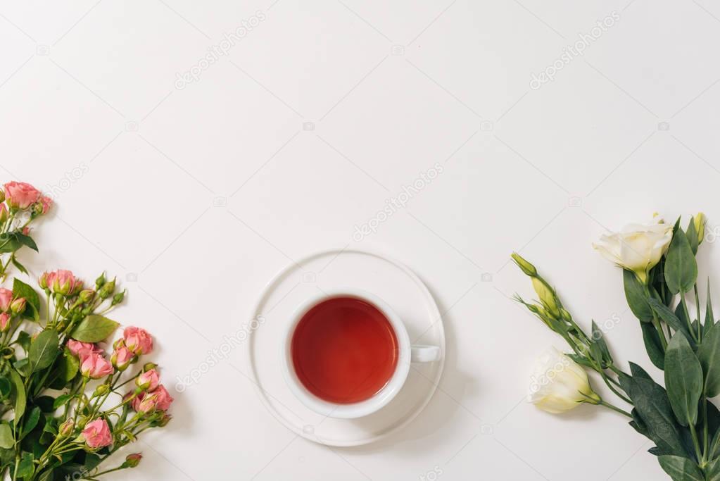 Flat lay of tea cup standing between flowers
