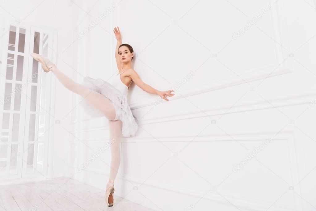 Graceful classical dancer stretching her left leg