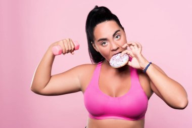 Chubby woman eating donut while exercising