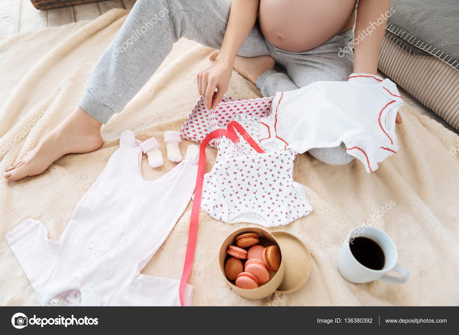 4d674459f Cerca de feliz joven embarazada posando con ropa de bebé Nueva Linda y  comida mientras reaxing y sentado en una sala acogedora — Foto de Dmyrto Z