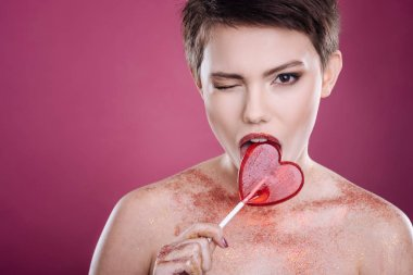 Pleasant young woman licking lollipop