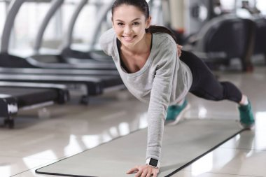 Smiling girl doing exercises in a gym.