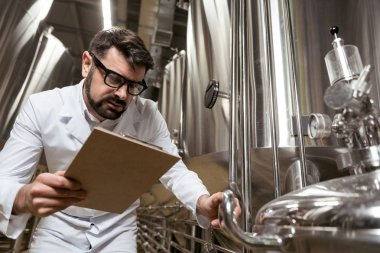 Amused man checking brewing mechanism
