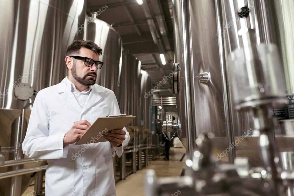 Serious man making notes in brewery