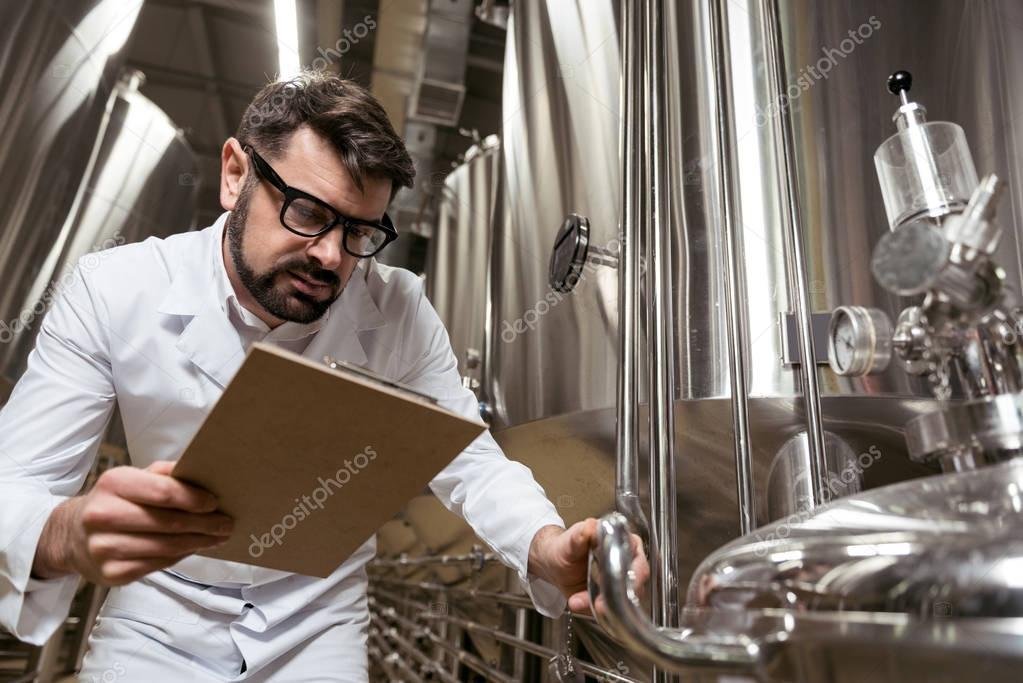 Amused man checking brewing mechanism