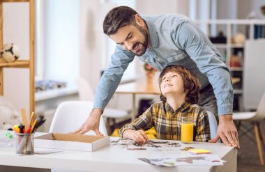 Positive delighted male standing behind son