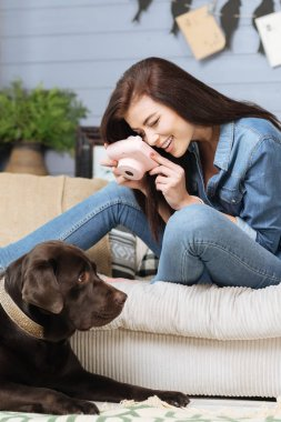 Fascinated young woman taking photos of her pet