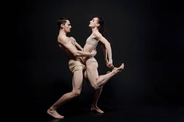 Undistracted dancers performing in the black colored studio