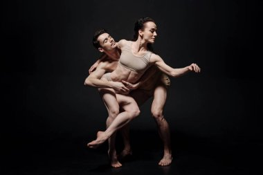 Enthusiastic ballet dancers acting together in the studio