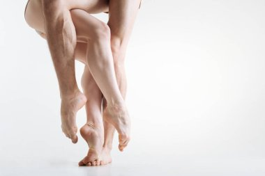Flexile graceful dancers legs performing in the white colored room