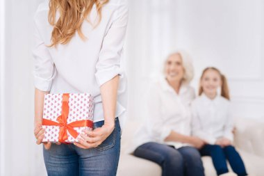 Pleasant adult woman holding present behind her back