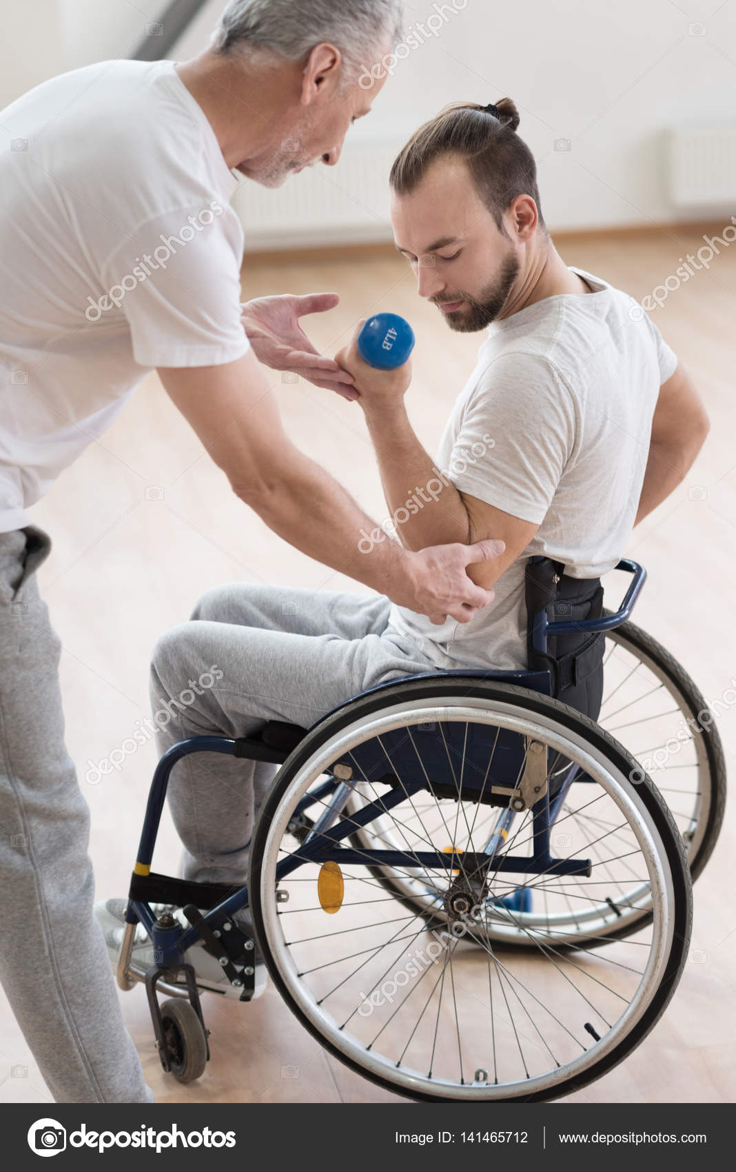 Involved disabled man exercising with his coach in the gym u stock