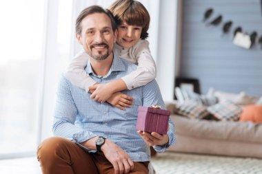 Handsome joyful man holding a gift box
