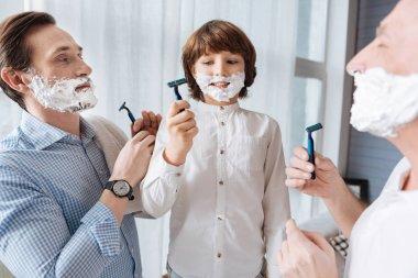 Nice delighted men holding razors