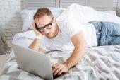 Příjemné vousatý muž doma pomocí přenosného počítače