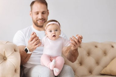 Joyful father having fun with his little daughter at home