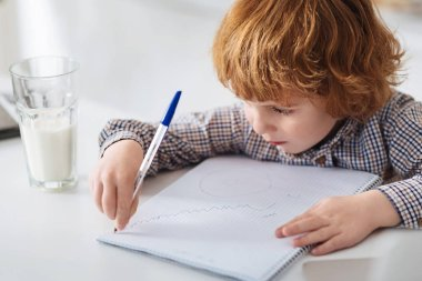 Creative clever boy making a drawing