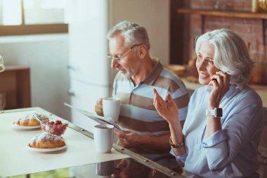 Positive aged couple having breakfast