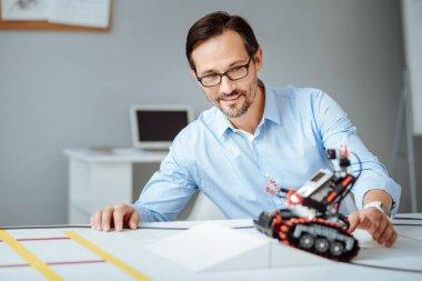 Professional joyful engineer testing the robot