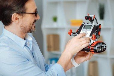 Joyful engineer testing robot