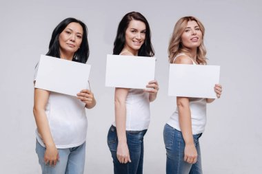 Women showing white pieces of paper